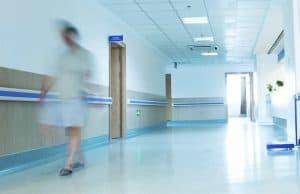 Nurse walking in hospital ward.