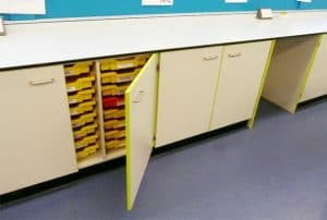 Trespa benching with yellow contrast edging cupboard and single yellow trays inside with one red tray.