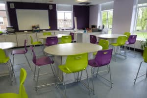 Science laboratory with purple and green chairs, showing teaching wall.