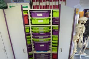 large storage cupboard with purple contrast edging and green and purple tray storage.