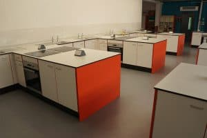 The Lakes School food technology classroom cabinets with orange contrast edging.