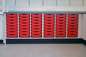 Bury College science lab prep room red tray storage.