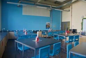 Blue contrast wall and co-ordinating stools in school science lab.