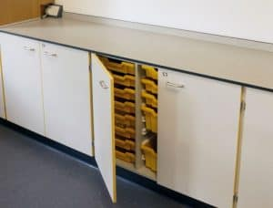 Trent College yellow tray storage in cupboard.
