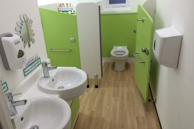 Green primary school sinks and toilet cubicles.