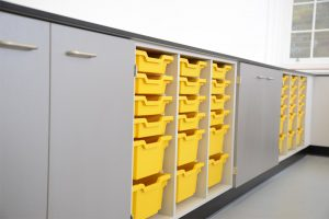 Royal Ballet School science laboratory with perimeter benching and yellow tray storage