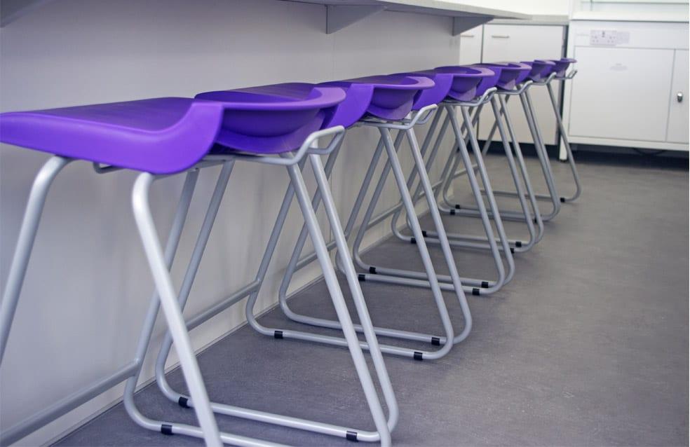 Contrast purple stools in school science lab.