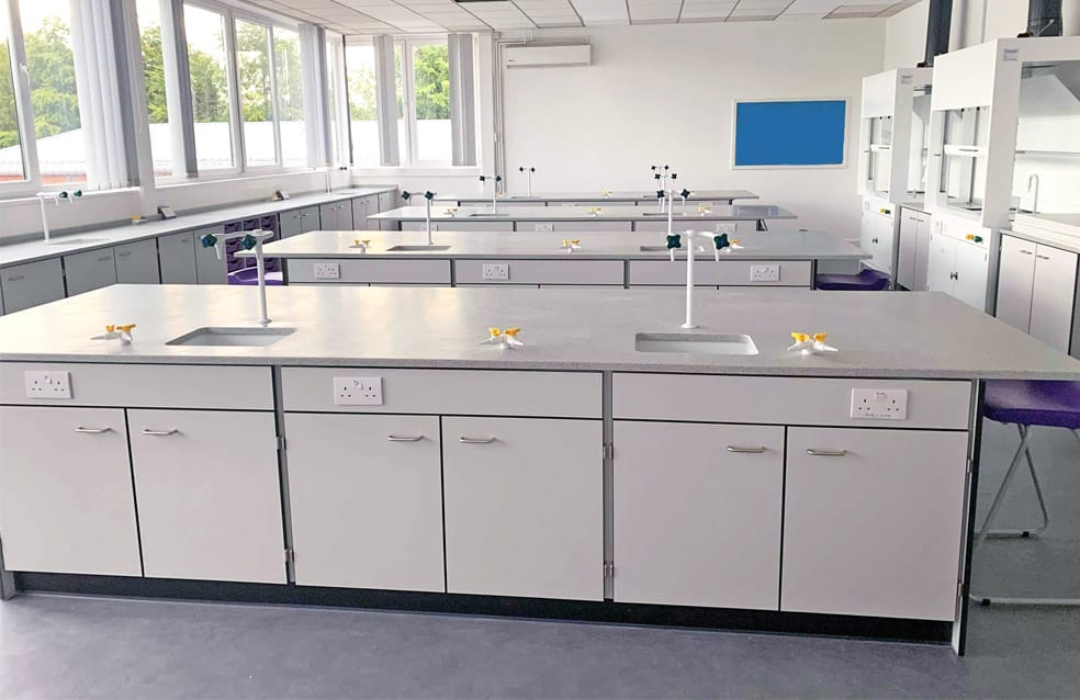 Integrated storage & ceramic sinks in school science laboratory.
