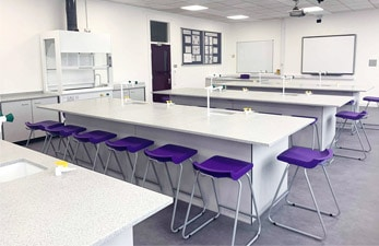Large islands with Velstone worktops in school science laboratory.